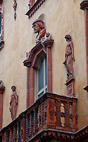Old carved wooden balcony with figural carvings on a beautiful old building in Lugano, Switzerland.