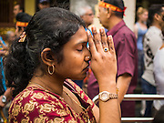 05 OCTOBER 2014 - GEORGE TOWN, PENANG, MALAYSIA: A woman prays during a procession honoring Durga in George Town during the Navratri procession. Navratri is a festival dedicated to the worship of the Hindu deity Durga, the most popular incarnation of Devi and one of the main forms of the Goddess Shakti in the Hindu pantheon. The word Navaratri means 'nine nights' in Sanskrit, nava meaning nine and ratri meaning nights. During these nine nights and ten days, nine forms of Shakti/Devi are worshiped.   PHOTO BY JACK KURTZ