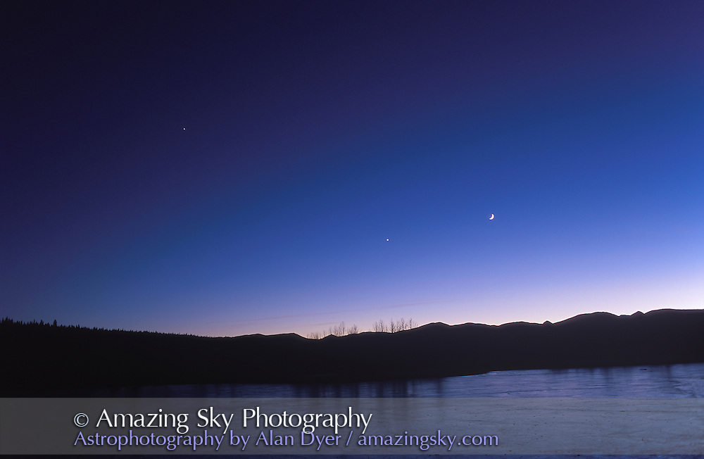 Planet Line-Up, Dec. 2, 1997 with (from left to right) Jupiter, Venus, Moon, in evening sky (Mars near Moon but hidden in twilight glow). Venus below ecliptic, Moon above it.<br /> <br /> Taken from site near Bragg Creek, Alberta. Ice is on pond. Sky colors exaggerated in Photoshop. Lighter exposure and earlier in evening than Dec. 2, 1997 shot on  Conjunctions Disc #1