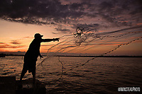 Fisherman Nery Hernandez of Raleigh tosses his casting net off the former Bogue Banks bridge at sunset at Atlantic Beach.