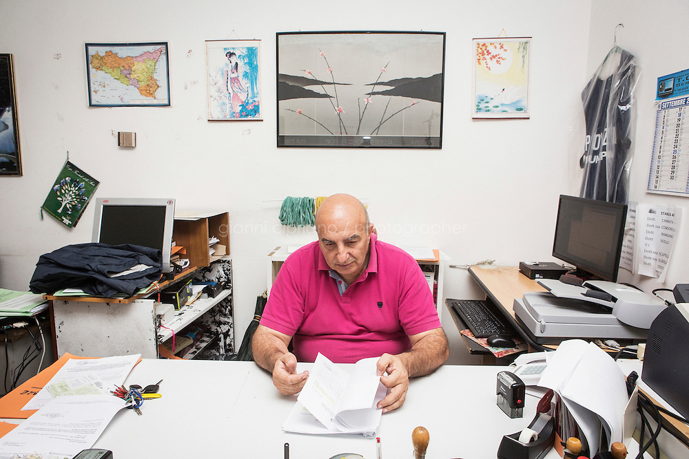 SIRACUSA, ITALY - 21 SEPTEMBER 2016: Angelo Milazzo (57), a local policeman in Siracusa formerly working in the Interagency Task Force for Combating Illegal Migration (or G.I.C.I.C., by its Italian acronym), shuffles through the files of the August 24th 2014 shipwreck for which he was assigned to identify 24 victims, in his office here in the Court House of Siracusa, Italy, on September 21st 2016.<br /> <br /> On August 24th 2014, a boat carrying more than 400 migrants, departed from the coasts of Libya in the attempt to reach Italy, capsized in international waters in the Mediterranean Sea. Rescuers of the Italian Navy saved 352 people, and recovered 24 lifeless bodies.<br /> <br /> Milazzo asked the public prosecutor for permission to open a Facebook profile under the name &ldquo;SIRIA-GICIC.&rdquo;  Relying on the descriptions of the bodies contained in the forensic reports, the photos taken on board the rescue ships and during the examinations, and on the collection of personal items that were found along with the corpses, he would work backwards from these slivers to try to arrive at the living people who once animated the now anonymous cadavers. Facebook, he hoped, would help him get the information he needed from the families of the missing to identify the bodies and allow him to inform their relatives of the death.<br /> <br /> The SIRIA-GICIC profile page on Facebook was created on October 10th, 2014, nearly two months after the shipwreck. At the time, 18 of the 24 bodies were still unidentified. Within a few months, Angelo Milazzo was able to identify all 24 bodies.<br /> <br /> Following the events of the Arab Spring in 2011, including Gaddafi&rsquo;s death and Libya&rsquo;s plunge towards chaos, clandestine crossings skyrocketed, as did the number of people drowning. In 2014 over 170,000 arrived in Italy and since then more than 10,000 perished in the Mediterranean sea.<br /> <br /> Only a fraction of these bodies have ever been recovered, and, of the ones that have, the majority remain unidentified. In Sicily alone there are mo