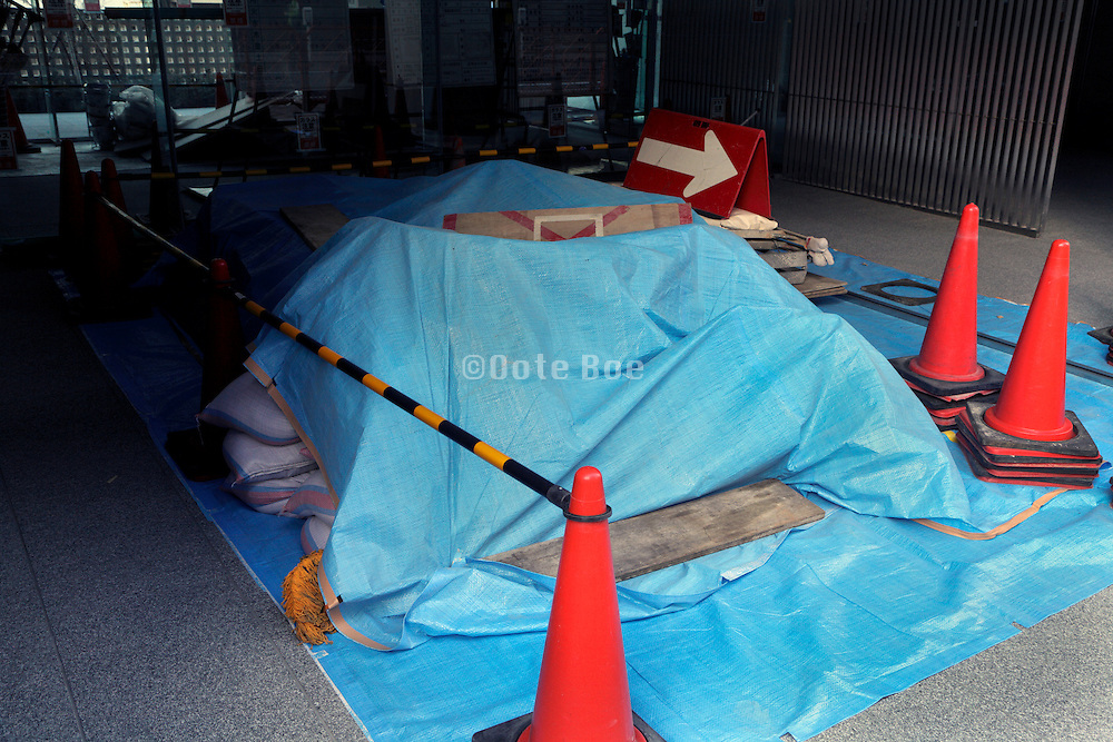 building construction material covered with a blue tarp and fenced with cones