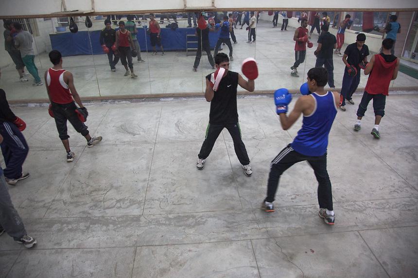 Dans le gymnase de Bhiwani Boxing Club, les élèves s'entraînent à couple; comme il n'y a que deux ring, ils utilisent aussi les autre espaces du gymnase