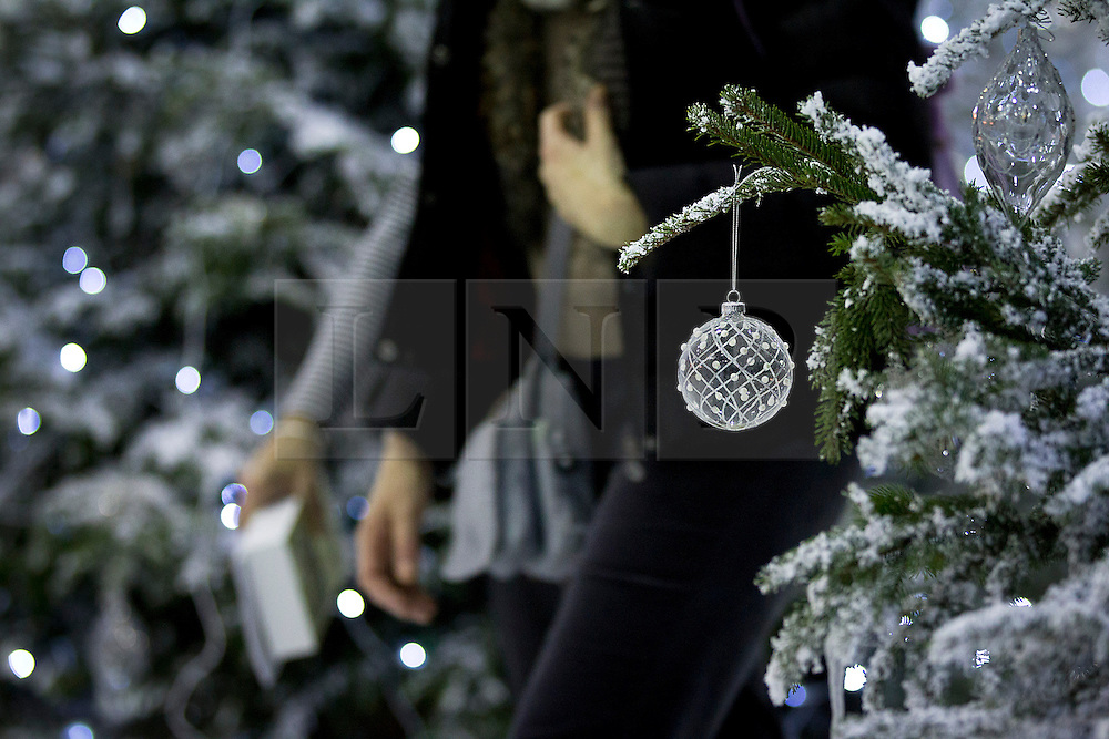 © Licensed to London News Pictures. 14/11/2012. London, UK. Visitors walk through Christmas trees at the opening of the 2012 Ideal Home at Christmas show at Earl's Court, London, today (14/11/12). The show, running from the 14th to the 18th of November features over 600 exhibitors across 6 sections including; Interiors & Furnishings, Food & Drink, Home Improvements & Outdoor Living, Fashion & Beauty, Technology & Gadgets and Gifts & Decorations. Photo credit: Matt Cetti-Roberts/LNP