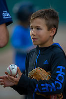 KELOWNA, CANADA - JUNE 28: A young bat boy gets autographs in the dugout during the opening charity game of the Home Base Slo-Pitch Tournament fundraiser for the Kelowna General Hospital Foundation JoeAnna's House on June 28, 2019 at Elk's Stadium in Kelowna, British Columbia, Canada.  (Photo by Marissa Baecker/Shoot the Breeze)