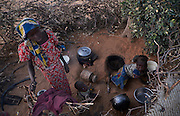 A girl minds her siblings in a makeshift kitchen in a camp of internally displaced people by the side of the road on the highway outside of Diffa, Niger on February 11, 2016.Caritas undertook a distribution of two blankets per family in January, 2016. Most of the displaced families are from the village of Chilori, Niger close to the border with Nigeria and fled when Boko Haram attacked killing 10 people.