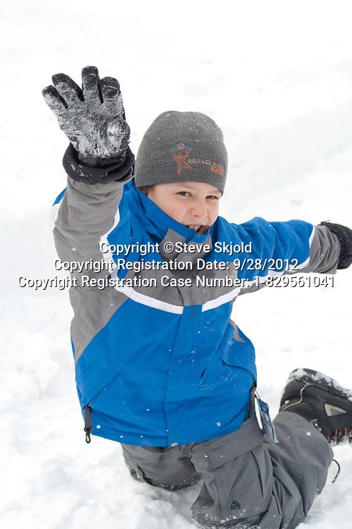 Boy age 10 having fun frolicking in the snow. St Paul Minnesota MN USA
