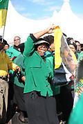 Een vrouw danst met een ANC banner met daarop een afbeelding van president Jacob Zuma.