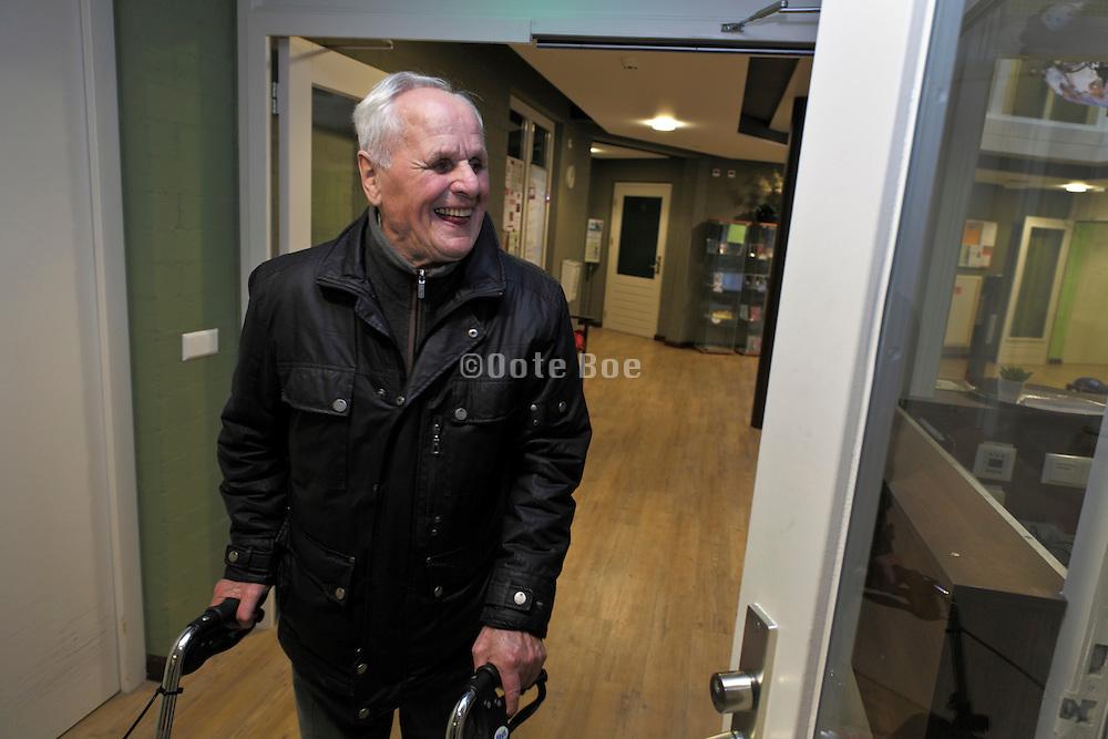 senior man with walker passing front desk inside a retirement home for the elderly