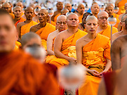 "22 FEBRUARY 2016 - KHLONG LUANG, PATHUM THANI, THAILAND:  Monks pray during Makha Bucha Day service at Wat Phra Dhammakaya.  Makha Bucha Day is a public holiday in Cambodia, Laos, Myanmar and Thailand. Many people go to the temple to perform merit-making activities on Makha Bucha Day, which marks four important events in Buddhism: 1,250 disciples came to see the Buddha without being summoned, all of them were Arhantas, Enlightened Ones, and all were ordained by the Buddha himself. The Buddha gave those Arhantas the principles of Buddhism, called ""The ovadhapatimokha"". Those principles are:  1) To cease from all evil, 2) To do what is good, 3) To cleanse one's mind. The Buddha delivered an important sermon on that day which laid down the principles of the Buddhist teachings. In Thailand, this teaching has been dubbed the ""Heart of Buddhism."" Wat Phra Dhammakaya is the center of the Dhammakaya Movement, a Buddhist sect founded in the 1970s and led by Phra Dhammachayo.     PHOTO BY JACK KURTZ"