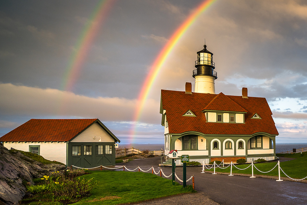 A vibrant rainbow fills the sky above Portland Head Light and Fort Williams Park in Cape Elizabeth, Maine.