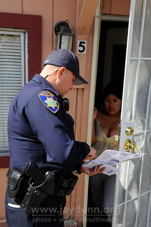 Salinas police officer Richard Lopez, who is bilingual, speaks in Spanish to a Fremont Street resident about CASP. The Community Alliance for Safety and Peace is an ambitious program that aims to steer youth away from gang violence and toward solutions offered by more than 30 local organizations offering alternatives.