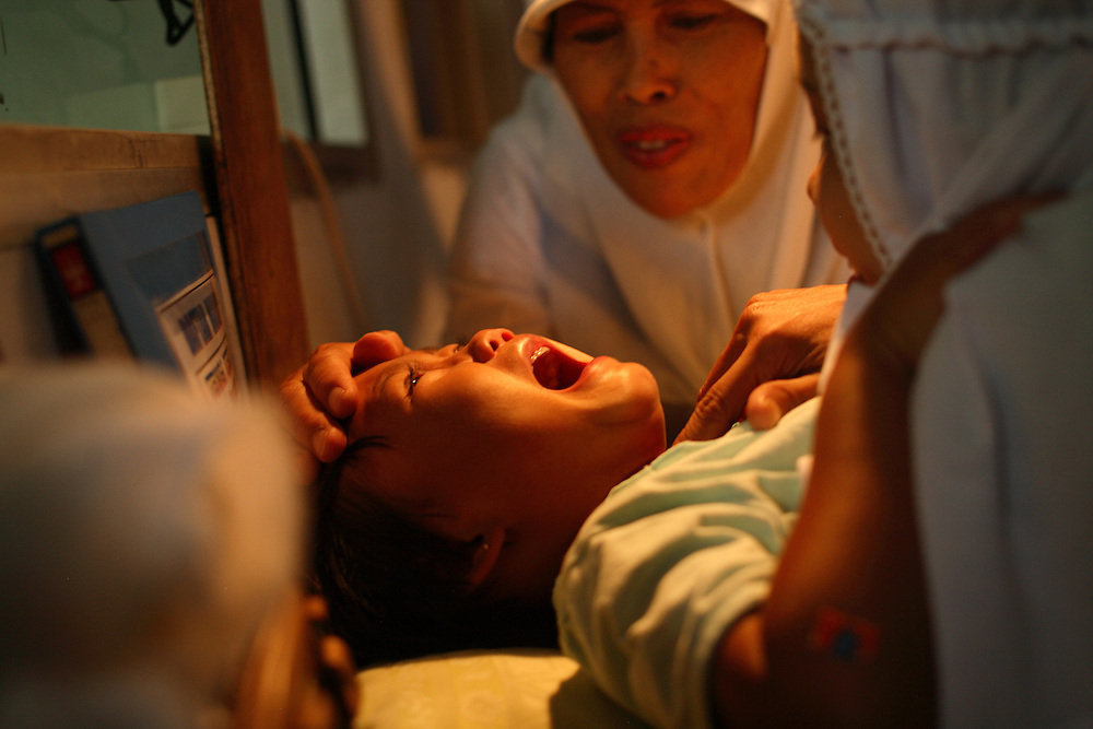 A young girl cries while being circumcised in Bandung, Indonesia on April  23, 2006.