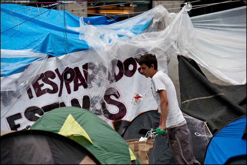 """Un manifestant dans la partie Sud du campement ou de nombreuses tentes sont installees. // Le mouvement spontane du """"15 M"""" (15 mai) compose de citoyens espagnols campe depuis 2 semaines sur la place Puerta Del Sol avec pour revendication la construction d'une democratie nouvelle. Organise en commission les citoyens prennent la parole lors d'assemblee ouverte a tous - Place Puerta Del Sol à Madrid le Juin 2011. ©Benjamin Girette/IP3Press"""