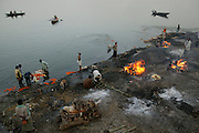 Male family members perform the rituals of Hindu cremation at the Harishchandra Ghat. Other fires burn bodies that have already had their cremation ritual.