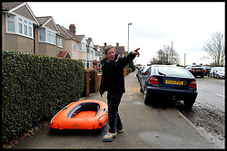 A resident of Egham pumps up an inflatable boat to use it to get to his house in flood hit  Egham, Surrey, United Kingdom, as floods hit Britain. Thursday, 13th February 2014. Picture by Andrew Parsons / i-Images