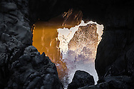 Splashing wave coming through evening lit sea cave at Pfeiffer Beach on the Big Sur Coast of Central California.