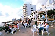 People enjoying daytime drinks at a seaside bar, Ibiza, Spain, 1990's