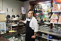 "NAPLES, ITALY - 12 DECEMBER 2014: Ciro Pipolo, a 45 years old barista, prepares an espresso coffee at Bar Settebello, a cafe that is part of the ""Rete del Caffè Sospeso"" (Suspended Coffee Network) in Naples, Italy, on December 12th 2014.<br /> <br /> A caffè sospeso,or suspended coffee, is a cup of coffee paid for in advance as an anonymous act of charity. The tradition began in the working-class cafés of Naples, where someone would order a sospeso, paying the price of two coffees but receiving and consuming only one. A poor person enquiring later whether there was a sospeso available would then be served a coffee for free."