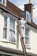 Painter on ladder painting wearing white protective overalls, Woodbridge, Suffolk, England, UK