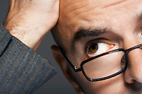 Balding businessman wearing glasses hand on head close up