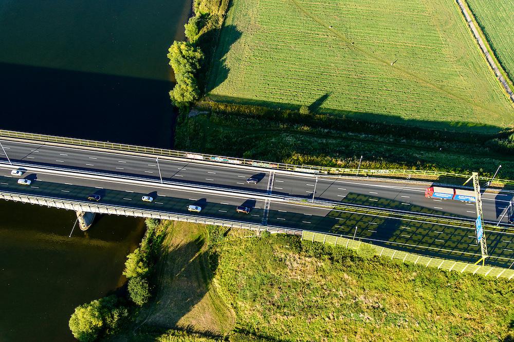 Nederland, Noord-Brabant, Den Bosch, 23-08-2016; brug in Rijksweg A2 over de Maas bij Empel met geluidsscherm in de karakteristiek huiskleur van Rijkswaterstaat. De schaduw op de weg kleurt geel door de lage avondzon. <br /> A2 motorway with bridge A2 over the Meuse at Empel. Yellow colored sound barrier.<br /> luchtfoto (toeslag op standard tarieven);<br /> aerial photo (additional fee required);<br /> copyright foto/photo Siebe Swart