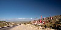 BANDERAS ROJAS EN UN PUESTO DE ADORACION A LA DIFUNTA CORREA, RUTA 89 Y CORDILLERA EN EL VALLE DE UCO, VOLCAN TUPUNGATO (6550 msnm) AL FONDO, TUPUNGATO, PROVINCIA DE MENDOZA, ARGENTINA