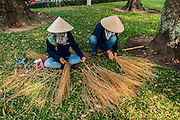 Gardeners make brooms for cleaning a park. Ho Chi Minh City (Saigon), Vietnam