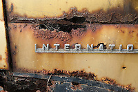 International Harvester nameplate on a rusted old yellow and black pick-up truck.