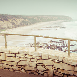 Laguna Beach Crystal Cove State Park panorama scenic overlook railing with the beach and Pacific Ocean in retro tone