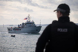 """© Licensed to London News Pictures. 09/01/2017. Portsmouth, UK.  A policeman on duty as the Polish Navy's youngest ship, ORP Kontradmiral Xawery Czernicki, (""""Czernicki"""") sail into Portsmouth Harbour under Police escort this morning, 9th January 2017. The multi-role support ship is visiting Portsmouth before deploying on a 6-month mission to join Standing NATO Maritime Group 2 (SNMG2) in the Mediterranean Sea. Photo credit: Rob Arnold/LNP"""