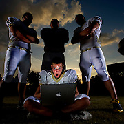 "Plant quarterback Phillip Ely checks out a message from one of his followers while the Plant lineman keep watch.  The top Hillsborough County High School football players Social Networking and portraits.  The theme a ""Tweet World."" [WILLIE J. ALLEN JR.,]."