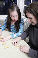 Maria Kopan, from Sylvania, Ohio (right) shows her daughter Katie how to make Koulourakia (butter cookies) as they prepare for a traditional Greek Orthodox Easter, Monday, March 24, 2008.