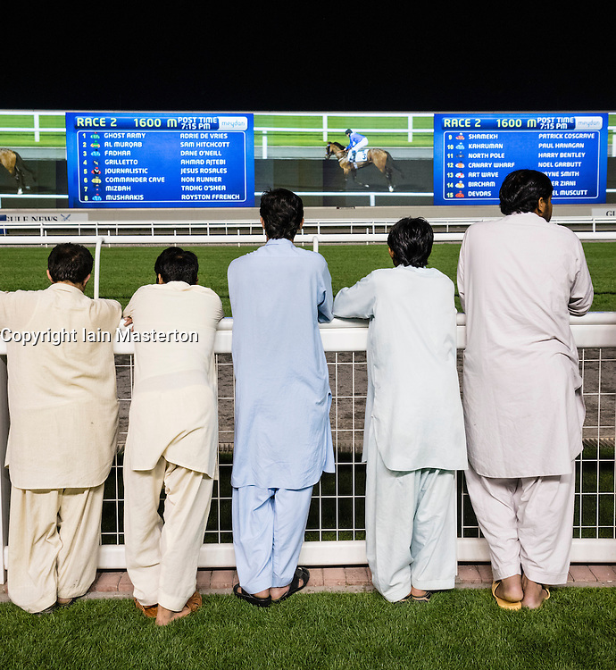 Men watching video screens at horse racing meeting at Al Meydan racecourse at night in Dubai United Arab Emirates