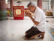 "26 AUGUST 2013 - BANGKOK, THAILAND: A man prays at the Poh Teck Tung Foundation during Hungry Ghost Month in Bangkok. Poh Teck Tung operates hospitals and schools and provides assistance to the poor in Thailand. The seventh lunar month (August - September in 2013) is when the Chinese community believes that hell's gate will open to allow spirits to roam freely in the human world for a month. Many households and temples will hold prayer ceremonies throughout the month-long Hungry Ghost Festival (Phor Thor) to appease the spirits. During the festival, believers will also worship the Tai Su Yeah (King of Hades) in the form of paper effigies which will be ""sent back"" to hell after the effigies are burnt.     PHOTO BY JACK KURTZ"