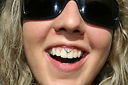young woman smiling with great white teeth and diamond piercing in her upper lip