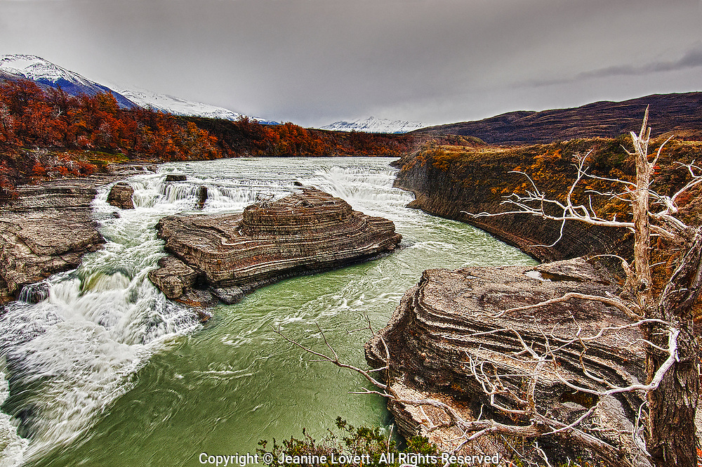 River from snow melt from Fritz Roy, Patagonia, and fall colors, with large rock formations in the foreground.