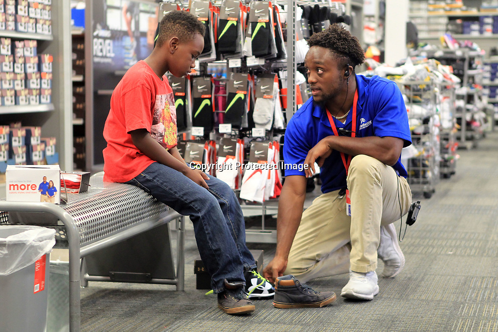 J'zentae Reed, 8, of Tupelo, has help from Marlon Sanders, an Academy Sports employee, with finding the correct size of football cleats Thursday morning in Tupelo. J'zentae is one of thirty children from the Tupelo Parks and Recreation that received $100.00 for their back-to-school shopping.