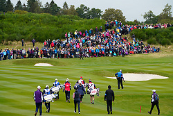 Auchterarder, Scotland, UK. 14 September 2019. Saturday morning Foresomes matches  at 2019 Solheim Cup on Centenary Course at Gleneagles. Pictured; Match 2 makes its way to 9th green with crowds of spectators on hillside beside the green. Iain Masterton/Alamy Live News