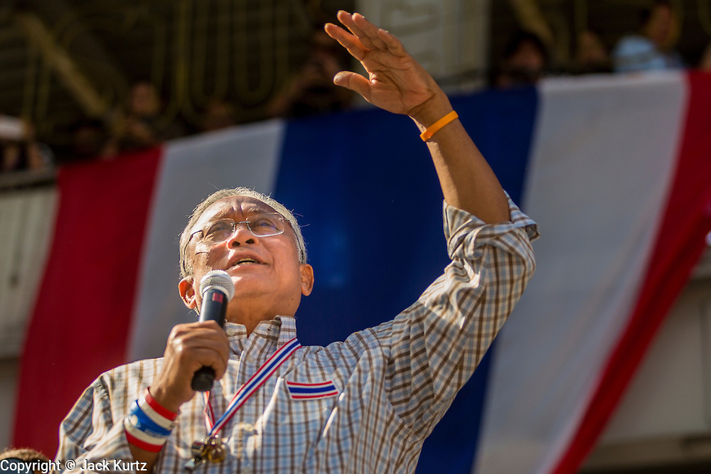 """15 JANUARY 2014 - BANGKOK, THAILAND: SUTHEP THAUGSUBAN, former Deputy Prime Minister of Thailand and leader of the Shutdown Bangkok anti-government protests, speaks from the stage at the protest site in the Asoke intersection. Tens of thousands of Thai anti-government protestors continued to block the streets of Bangkok Wednesday to shut down the Thai capitol. The protest, """"Shutdown Bangkok,"""" is expected to last at least a week. Shutdown Bangkok is organized by People's Democratic Reform Committee (PRDC). It's a continuation of protests that started in early November. There have been shootings almost every night at different protests sites around Bangkok. The malls in Bangkok are still open but many other businesses are closed and mass transit is swamped with both protestors and people who had to use mass transit because the roads were blocked.    PHOTO BY JACK KURTZ"""
