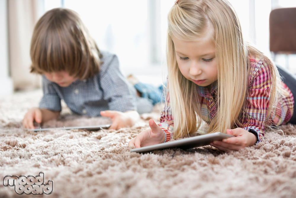 Cute girl and brother using digital tablets on rug in living room