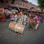 A drummer rushes though the crowd at Teej.