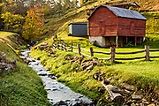Prices Creek flowing past autumn foliage and an old red barn along the Quilt Trails in Prices Creek, North Carolina.