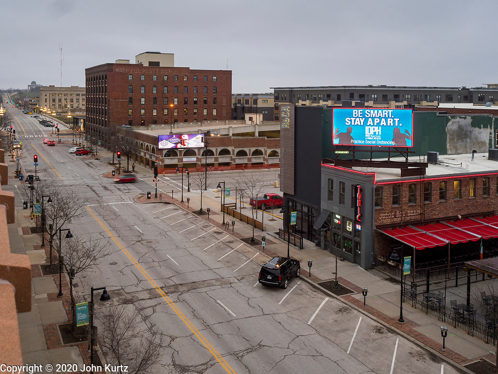 "24 MARCH 2020 - DES MOINES, IOWA: A public service announcement about the coronavirus on an electronic billboard in the historic district of downtown Des Moines. Des Moines was virtually deserted Tuesday as many people chose to stay in their homes. On Tuesday morning, 24 March, Iowa reported over 120 confirmed cases of the Coronavirus (SARS-CoV-2) and COVID-19. Restaurants, bars, movie theaters, places that draw crowds are closed for at least 30 days. The Governor has not ordered ""shelter in place""  but several Mayors, including the Mayor of Des Moines, have asked residents to stay in their homes for all but the essential needs. People are being encouraged to practice ""social distancing"" and many businesses are requiring or encouraging employees to telecommute.      PHOTO BY JACK KURTZ"