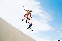Two late 20's Caucasian men leaping off a sand dune.  Near Vantage, Washington, USA.  Frenchmans Coulee.