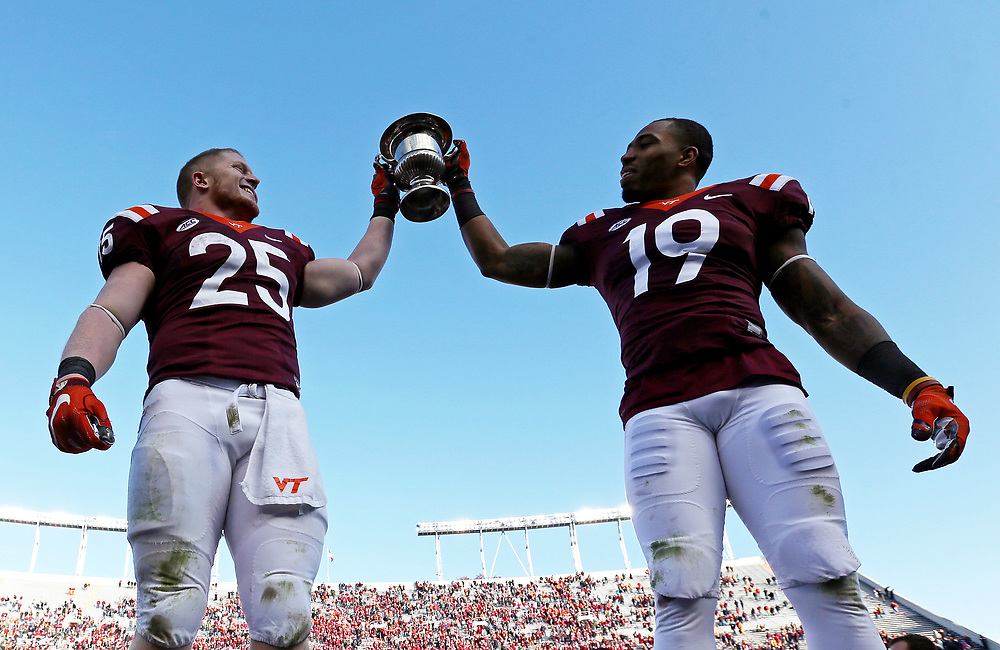 iNov 26, 2016; Blacksburg, VA, USA;  Virginia Tech Hokies running back Sam Rogers (25) and Virginia Tech Hokies defensive back Chuck Clark (19) celebrate with the Commonwealth Cup after beating the Virginia Cavaliers at Lane Stadium. Mandatory Credit: Peter Casey-USA TODAY Sports