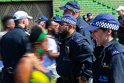 People make their way towards the carnival through a line of police officers as day one, Children's Day, of the Notting Hill Carnival gets underway in London. London, August 25 2019.