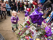 "22 APRIL 2016 - MINNEAPOLIS, MN: A child wearing a purple parka looks at a memorial for Prince in front of 1st Ave in Minneapolis. Minnesotans were urged to wear purple Friday in honor of Prince. Thousands of people came to 1st Ave in Minneapolis Friday to mourn the death of Prince, whose full name is Prince Rogers Nelson. 1st Ave is the nightclub the musical icon made famous in his semi autobiographical movie ""Purple Rain."" Prince, 57 years old, died Thursday, April 21, 2016, at Paisley Park, his home, office and recording complex in Chanhassen, MN.    PHOTO BY JACK KURTZ"