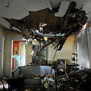 Frances Lukens looks at the tangle of boards and tree limbs piercing her living room ceiling in Lynchburg, Va. on Saturday, after a huge oak tree fell directly on the house during the storm the previous night.<br />   (Photo by Parker Michels-Boyce/The News &amp; Advance)