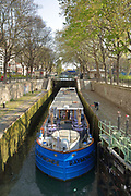 Canal barge in the Ecluse des Morts lock, in the Canal Saint-Martin, in the 10th arrondissement of Paris, France. The Canal Saint-Martin is a 4.6km long waterway between the Canal de l'Ourcq and river Seine, built 1802-25 to provide a fresh water source to the city and provide a trade route for canal barges. Picture by Manuel Cohen